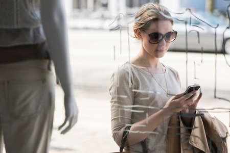 Young woman checking mobile phone outside fashion shop