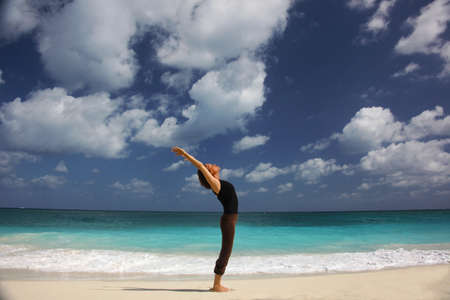 Mature woman doing yoga on beach,Paradise Island,Nassau,Bahamas