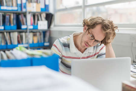 Young man with head in hands in creative office