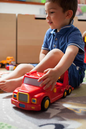 Boy playing with toy car on play mat
