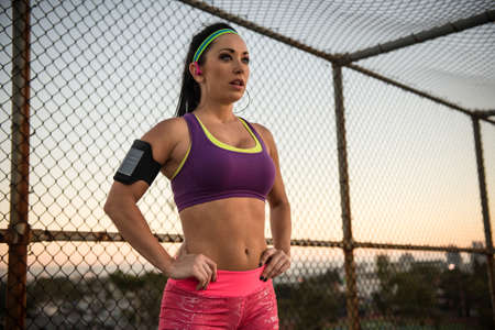 alice band: Female runner with hands on hips listening to mp3 player