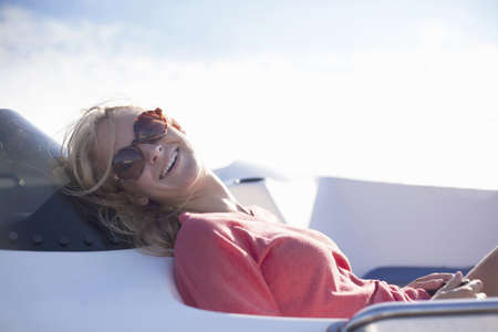Woman wearing sunglasses laughing on yacht,Wales,UK