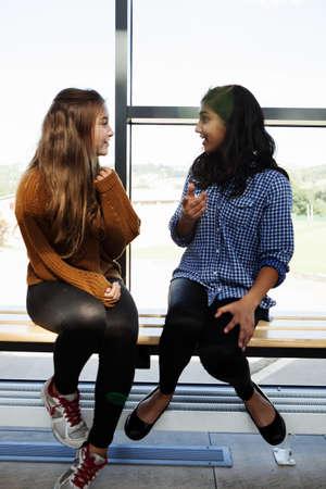 low self esteem: Two teenage schoolgirls sitting chatting in corridor