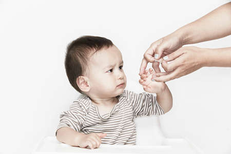 Hands applying plaster to babys finger