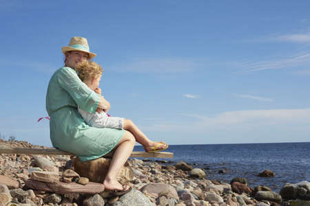 sunhat: Mother and daughter sitting on beach,Eggergrund,Sweden