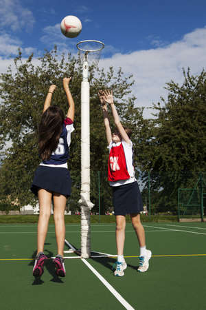 Two schoolgirls playing netball LANG_EVOIMAGES