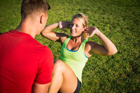 exerting: Young woman in park with trainer doing sit-ups LANG_EVOIMAGES