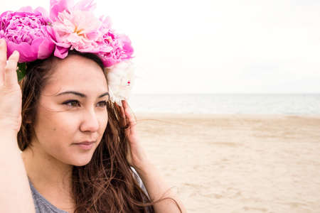 Young woman on beach with flowers in her hair LANG_EVOIMAGES
