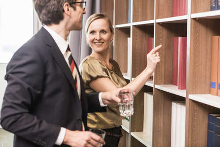 Woman pointing at books on bookcase