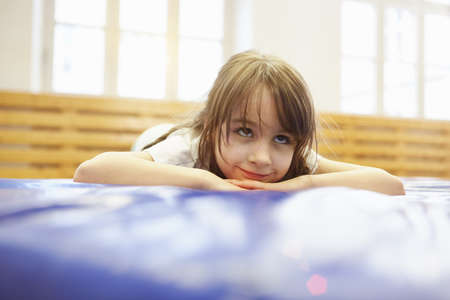 Girl lying on front on blue exercise mat LANG_EVOIMAGES