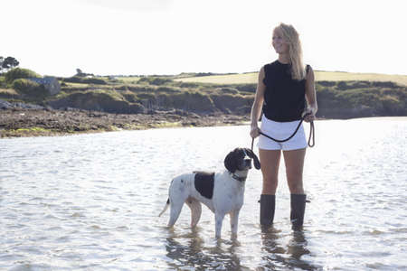 Woman standing with dog in water,Wales,UK