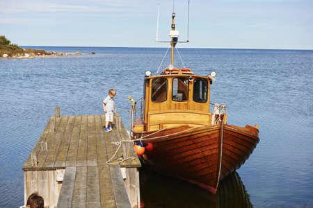 Boy on pier by boat,Eggergrund,Sweden