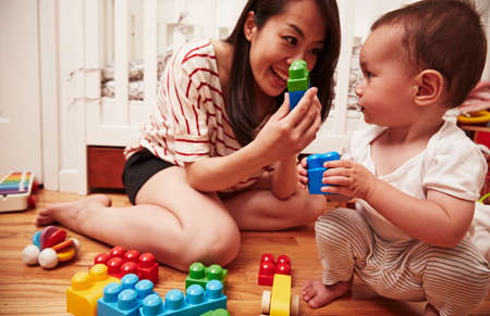 woman hanging toy: Mother and baby boy playing with building blocks