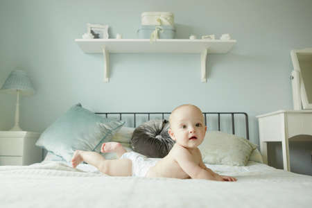 nappy new year: Baby boy lying on front on bed LANG_EVOIMAGES
