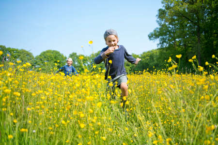 Brothers running through long grass and flowers
