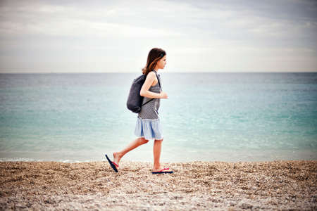 Girl walking by the sea LANG_EVOIMAGES