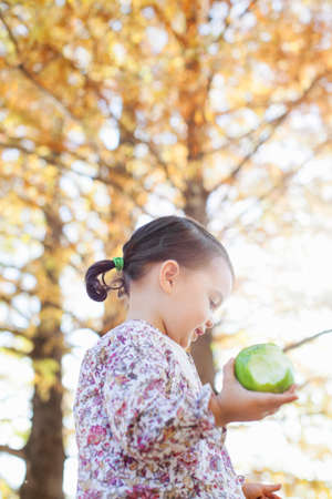curiousness: Child holding bitten green apple