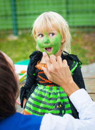 Man painting childs face green LANG_EVOIMAGES