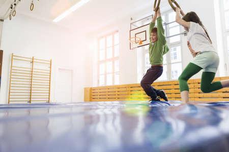 Girls hanging on gymnastic rings in school gymnasium