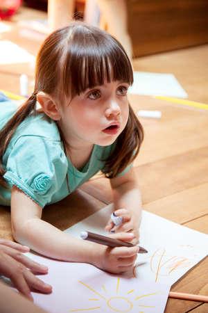 Girl lying on floor drawing
