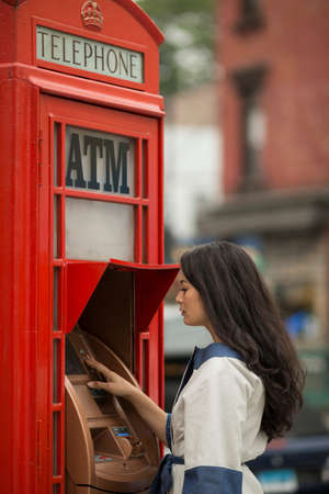 Mid adult women using cash machine in a public telephone box LANG_EVOIMAGES