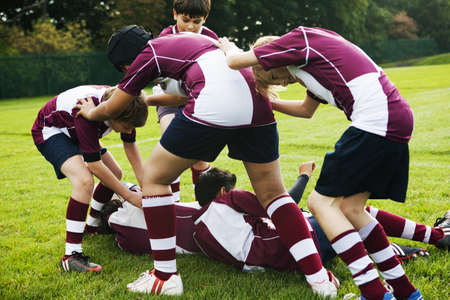 Teenage schoolboy rugby team playing aggressively
