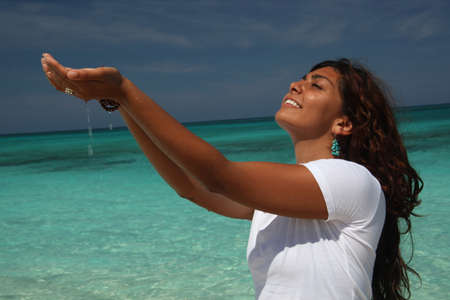 sleeve: Young woman on beach with hands cupping water,Paradise Island,Nassau,Bahamas