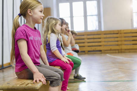 Children sitting on bench in school hall