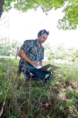 Young man sitting in field using laptop