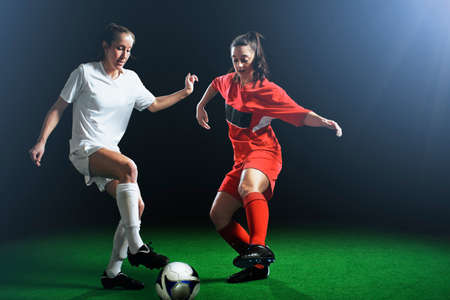 move in: Two female soccer players tackling ball
