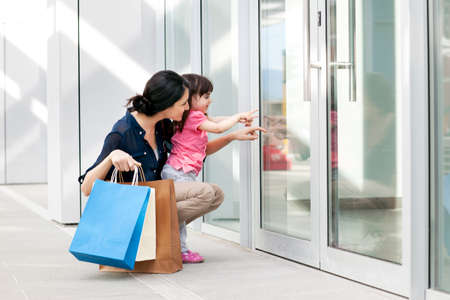 Mother and daughter pointing at shop window