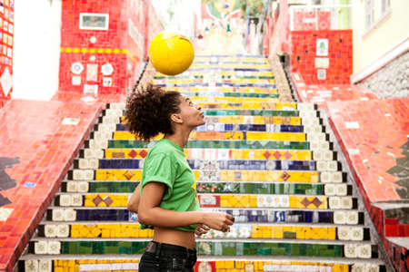sleeve: Young woman doing keepy uppys in front of the Escadaria Selaron steps in Rio de Janiero,Brazil
