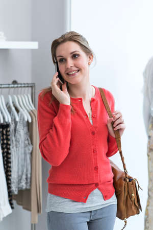 coathangers: Young woman on mobile phone in fashion shop