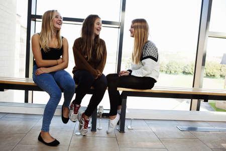 low self esteem: Three teenage schoolgirls sitting chatting in corridor