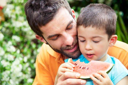 Father holding slice of watermelon,son eating it