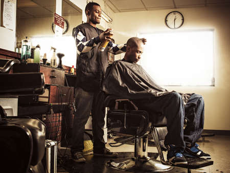 reminisce: Barber in traditional barber shop spraying hairspray on man