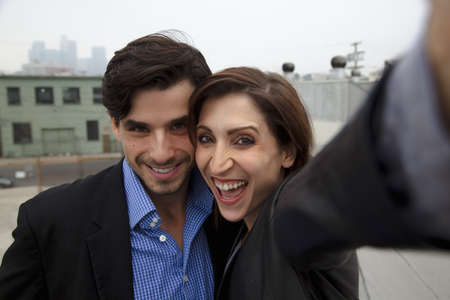 Couple taking self portrait on city rooftop