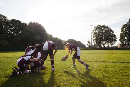 Teenage schoolboy rugby team taking ball from huddle LANG_EVOIMAGES