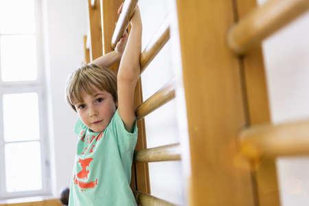 Boy hanging on climbing frame at school