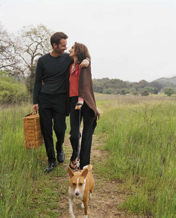 Couple with picnic basket walking dog LANG_EVOIMAGES