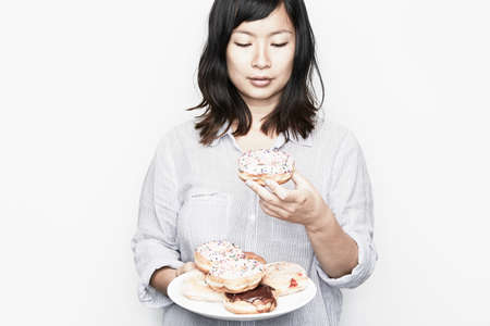 unfit: Pregnant woman holding plate of doughnuts