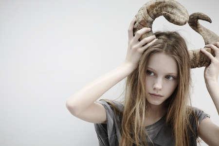 Portrait of girl holding horns on her head