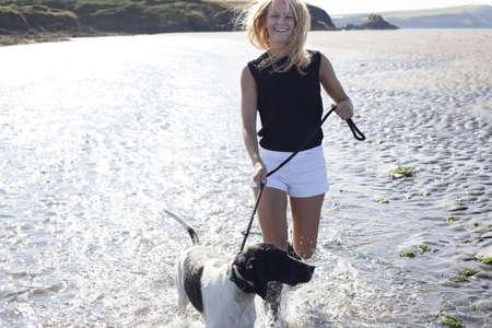 Woman walking dog on beach,Wales,UK LANG_EVOIMAGES