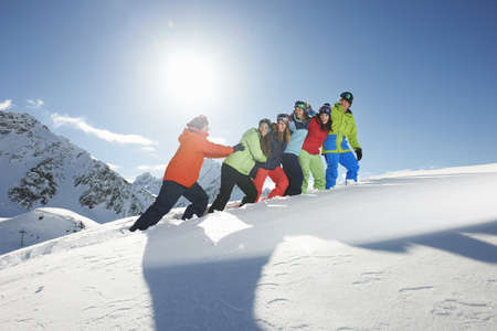 Man pushing friends uphill in snow,Kuhtai,Austria