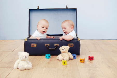 Two baby boys sitting in suitcase looking at toys LANG_EVOIMAGES