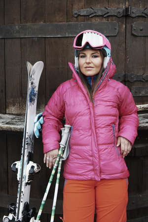 Young woman leaning against door,wearing skiwear and carrying ski equipment
