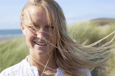 Portrait of woman with long blonde hair wearing earphones,Wales,UK LANG_EVOIMAGES