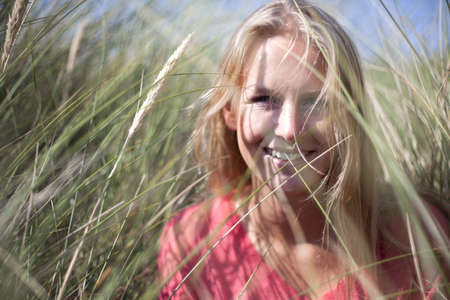 obscuring: Portrait of blonde woman in marram grass,Wales,UK LANG_EVOIMAGES