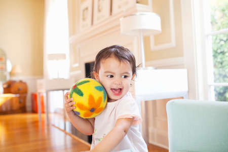 Talking baby girl with yellow floral ball on face LANG_EVOIMAGES