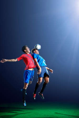 Male soccer players heading ball